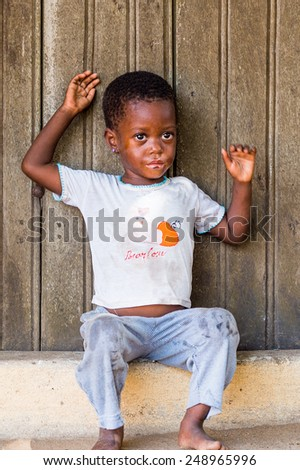LOME, TOGO - MAR 9, 2013: Unidentified Togolese little girl sit at the porch of a house. People of Togo suffer of poverty due to the unstable economic situation.
