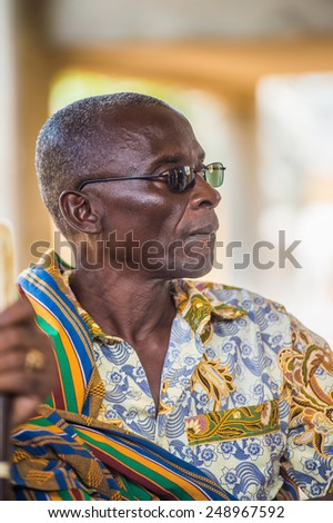 LOME, TOGO - MAR 9, 2013: Unidentified Togolese man in traditional clothes wearing glasses portrait . People of Togo suffer of poverty due to the unstable economic situation.