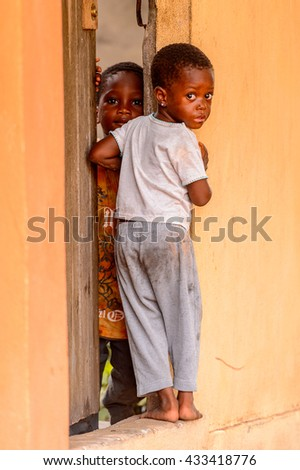 LOME, TOGO - MAR 9, 2013: Unidentified Togolese two little girls near a door of a local house. People of Togo suffer of poverty due to the unstable economic situation.