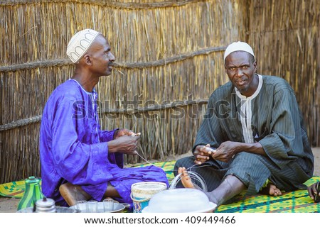 LOMPOUL/SENEGAL - NOVEMBER 13, 2013: Two unidentified senegalese men sitting and working in a native tribe village near Lompoul, Senegal - stock photo
