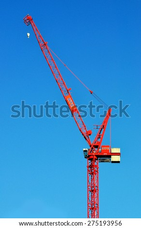 LONDON - APRIL 18, 2015. A HTC crane helps build new apartments, transforming the landscape of Stratford; part of a huge regeneration programme from industrial wasteland in east London, UK. - stock photo