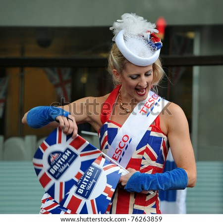 LONDON - APRIL 29: A representative of Tesco supermarkets hands out Union Jack flags in celebration of the wedding of Prince William and Catherine Middleton in Trafalgar Square on April 29, 2011 in London, England. - stock photo