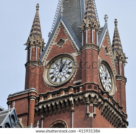 LONDON - APRIL 10, 2016. Fine  details of the clock tower at the 1868 St Pancras International railway station and hotel, designed by Sir George Gilbert Scott, in the King's Cross area of London. - stock photo