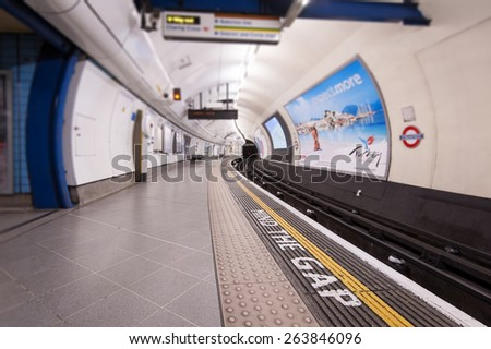 LONDON - APRIL 14, 2013: Mind the Gap sign in Tube Station. The Underground system serves 270 stations and has 402 kilometres (250 mi) of track, 45 per cent of which is underground. - stock photo