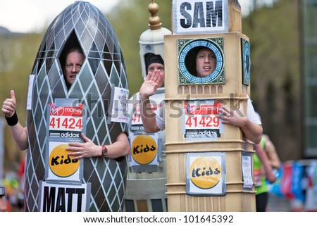 LONDON - APRIL 22: Three fun runners in the 2012 London marathon, wearing costumes of prominent London buildings, pause for a breath as they reach the 23 mile mark on April 22, 2012 in London - stock photo