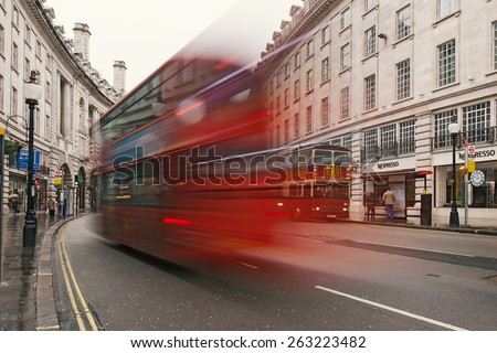 LONDON - APRIL 12, 2013: Traffic in Regent Street with Double decker red bus blurred. Regent Street is one of the major shopping streets in London's West End, well known to tourists and Londoners. - stock photo