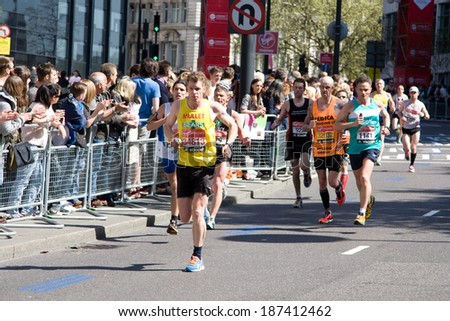 LONDON - APRIL 13: Unidentified men run the London marathon on April 13, 2014 in London, England, UK. The marathon is an annual event.  - stock photo