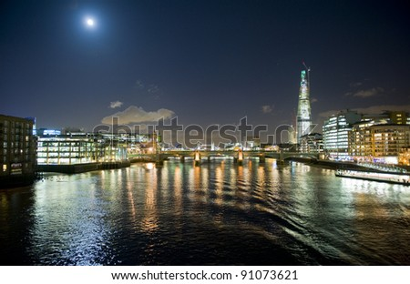 London at night with the Moon. - stock photo