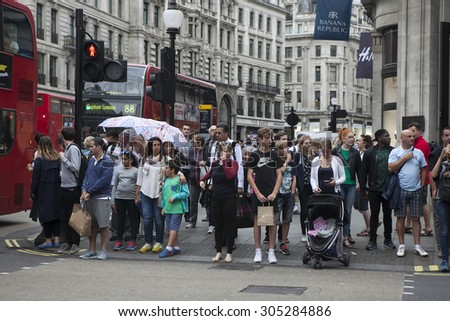 LONDON - AUG 10 : Crowd passing oxford circus on Aug 10, 2015, London, UK. Oxford Circus, busy intersection with Regent Street, is biggest shopping street in Europe, visited by millions of tourists