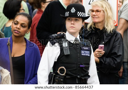 LONDON - AUG 28: policewoman patrols the street of  Notting Hill during the famous annual caribbean  Carnival on August 29, 2011 in London, England. - stock photo