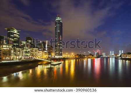 LONDON - AUGUST 22: A skyscraper and modern buildings in the St George Wharf quarter in Vauxhall, London at night with the Battersea Power Station in the background on August 22, 2013 - stock photo