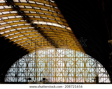 LONDON - August 2: Iron arch at Paddington station on August 2, 2014 in London, UK. The glazed roof is supported by large wrought iron arches in three spans, spanning 68 feet, 102 feet, and 70 feet.  - stock photo
