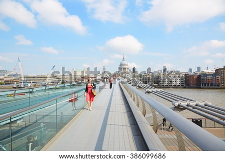 LONDON - AUGUST 8: Millennium bridge with people walking and St Paul cathedral in a sunny morning on August 8, 2015 in London. The footbridge crosses the river Thames.