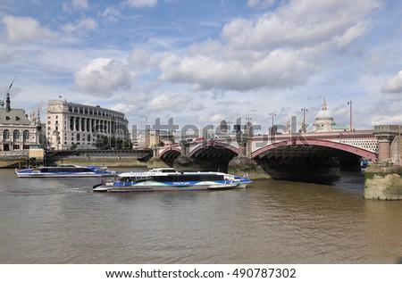 LONDON - AUGUST 13, 2016. Pleasure boats pass under Blackfriars Bridge on the River Thames. The road crossing was designed by Joseph Cubitt and opened by Queen Victoria in 1869 in central London.