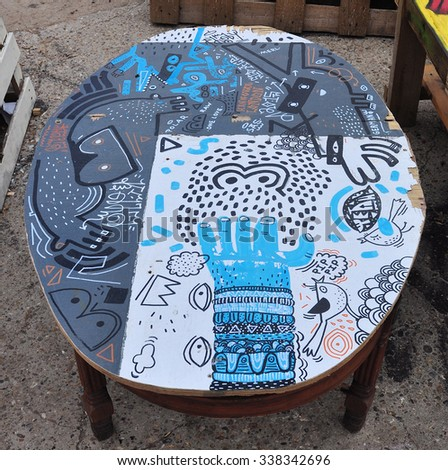 LONDON - AUGUST 1, 2015. Street art applied to a table in the Nomadic Community Gardens at Shoreditch in the Borough of Tower Hamlets, an area renown for its public painting in east London, UK.
