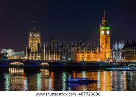 London Big Ben parliament Thames with boat and bridge in night - stock photo