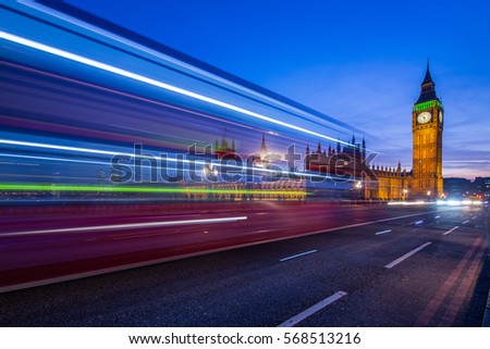 London bus rushing past the camera with Big Ben London England in the background at dusk