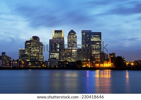 London business district panorama with colorful reflections on the Thames River, against dramatic night sky - stock photo