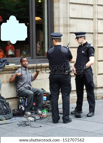 LONDON � CIRCA AUGUST 2007: Unknown police officers make an arrest of unknown street musician in middle-city on August 2007 in London, Great Britain. - stock photo