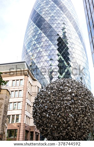 London cucumber skyscraper with an architectural statue - a huge metal ball in front of it in London - stock photo