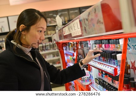 LONDON - DEC 12: A shopper browses a shelf in a Boots pharmacy on Dec 12, 2014 in London, UK. Founded in 1849 Boots has grown from a family business to a multinational employing over 120,000 staff.