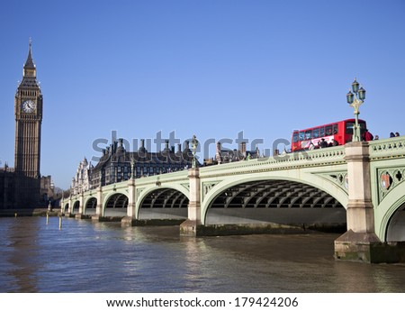 LONDON - DEC 21: Iconic London bus crossing Westminster Bridge in the United Kingdom December 29, 2013 in London, England - stock photo