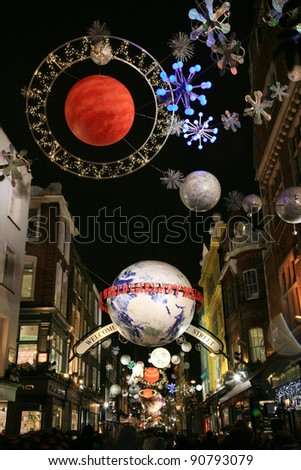 LONDON - DECEMBER 16: Christmas Lights Display on Carnaby Street on December 16, 2010 in London, England. The modern colorful Christmas lights attract and encourage people to the street.