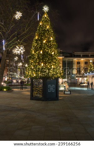 LONDON - DECEMBER 21st 2014: Christmas tree and lights decorations on Duke of York Square offers a range of international retailers and leading restaurant alongside the iconic Saatchi Gallery. - stock photo