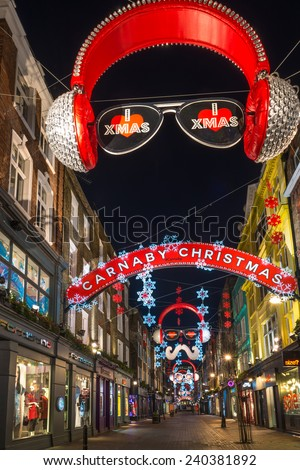 LONDON - DECEMBER 29th 2014: Christmas lights on Carnaby Street, London UK. The Carnaby Christmas lights have a distinctive theme for 2014 to celebrate it's reputation as a unique shopping destination - stock photo