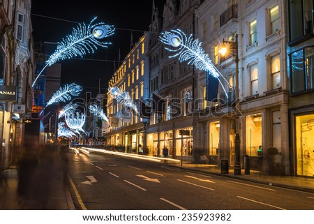 LONDON - DECEMBER 6th 2014: Christmas lights on New Bond Street. The already glamorous area has been given a glittering makeover for the Christmas season with sprays of peacock-inspired decorations. - stock photo