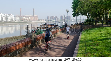 London, England - April 30, 2014: A cyclist and a jogger using the River Thames path in Battersea on a morning with visible smog. - stock photo
