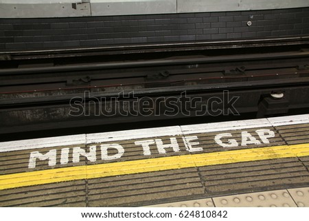 LONDON, ENGLAND - 20 APRIL 2017: A sign painted on a platform on the London Underground warns commuters to MIND THE GAP. The phrase was first introduced in 1969 on the London Underground. Editorial