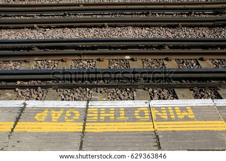 LONDON, ENGLAND - 20 APRIL 2017: A sign painted on a platform on the London Underground warns commuters to MIND THE GAP. The phrase was first introduced in 1969 on the London Underground. Editorial.