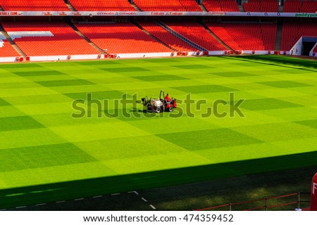 LONDON, ENGLAND - APRIL 22: Man on ride on lawn watering machine, The Emirates Stadium, Arsenal Football Club. In London, England. On 22nd April 2010.
