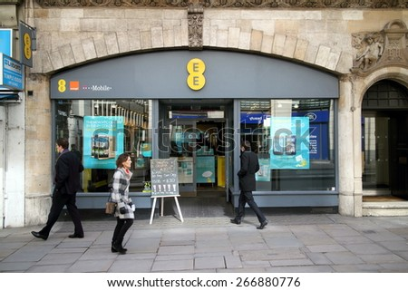 London, England - April 02, 2015: People passing and entering an EE store in London, England. EE delivers mobile and fixed communications services and includes the Orange and T-Mobile companies - stock photo