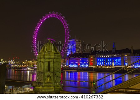 London, England - April 8, 2016: Westminster's London Eye lit up with pink lights on the 8th of April 2016 in London, England.  - stock photo