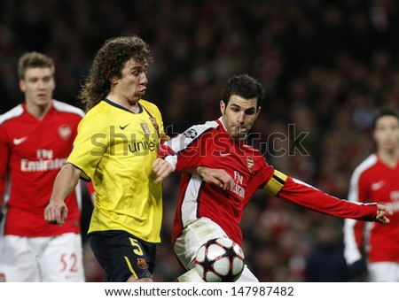 LONDON, ENGLAND. 31/03/2010. Barcelona's Carles Puyol fouls Arsenal'sCesc Fa?bregas to concede a penalty during the  UEFA Champions League quarter-final at the Emirates Stadium - stock photo