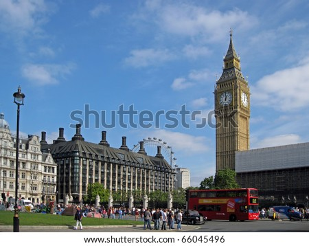 LONDON, ENGLAND - Big Ben with double-decker bus in foreground and London Eye in background.