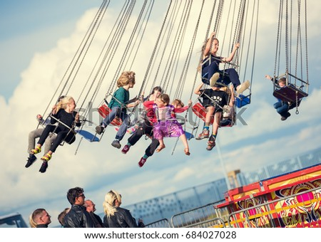 London, England, 05/05/2017 Children Swinging In The Air On A