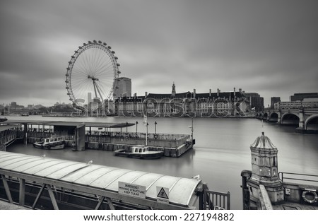 LONDON - ENGLAND, DECEMBER 25th, 2010: Gloomy, Black and White image of the Shouth Bank of River Thames. This view including: London Eye, County Hall and Westminster Millennium Pier.  - stock photo