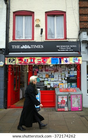 London, England - February 04, 2016: A pedestrian passes by a typical newsagent store in the town center of Richmond, London UK - stock photo