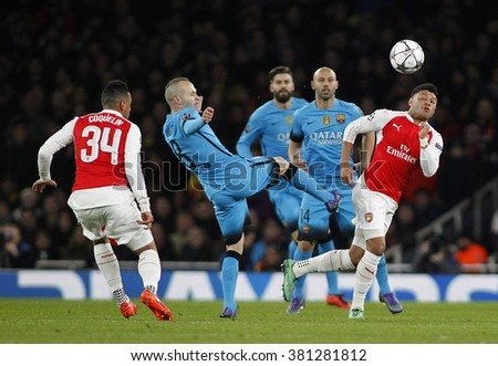 LONDON, ENGLAND - FEBRUARY 23: Andres Iniesta of Barcelona and Alex Oxlade-Chamberlain of Arsenal compete for the ball during the Champions League match between Arsenal and Barcelona - stock photo