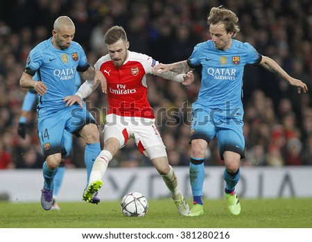 LONDON, ENGLAND - FEBRUARY 23: Javier Mascherano and Ivan Rakitic of Barcelona compete for the ball with Aaron Ramsey of Arsenal during the Champions League match between Arsenal and Barcelona  - stock photo