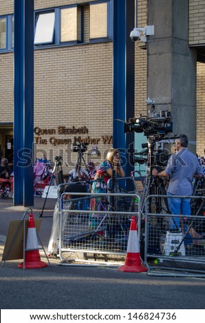 LONDON, ENGLAND - JULY 19: A bored looking television reporter and crew outside St Mary's Hospital, Paddington on July 19 2013.  Journalists are waiting for the Duchess of Cambridge to give birth.