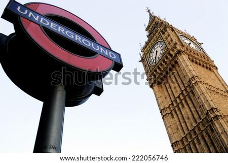 LONDON, ENGLAND - JULY 1, 2014: London Underground sign and the Big Ben. The London Underground is the oldest underground railway in the world covering 402 km of tracks. - stock photo