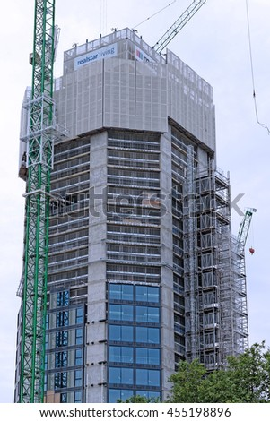 LONDON, ENGLAND - JULY 8, 2016: New apartment building in construction, part of a huge regeneration program of Borough of Southwark to transform the landscape of Elephant and Castle area. - stock photo