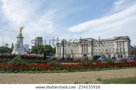 London, England - July 29th 2014: Tourists and black Cabs outside Buckingham palace and the Victoria monument - stock photo