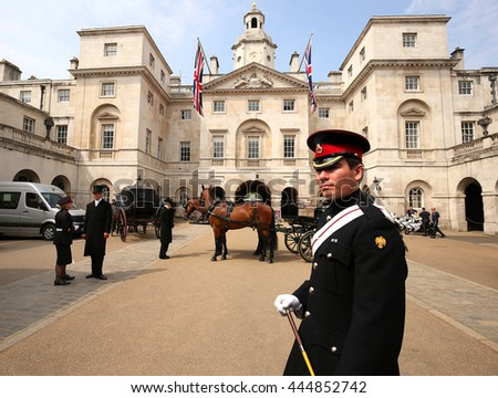 LONDON, ENGLAND, MAY 28, 2016:  The Queen's Horse Guard stands on duty at the entrance of the Horse Guards building as the horse drawn carriages and motorbikes are readied for an official event.  - stock photo