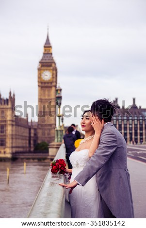 LONDON - ENGLAND 25 OCTOBER 2015 - Picture of bride and groom with Big Ben and the The Houses of Parliament as they embrace each other during an overcast day in LONDON ON OCTOBER 2015. - stock photo
