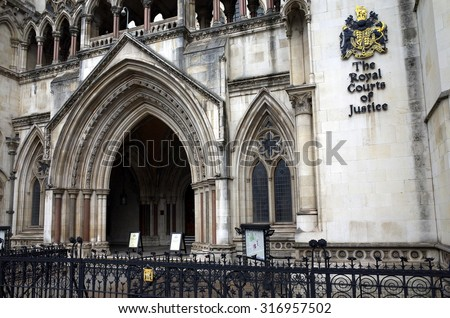 London, England - Sept 09, 2015: Exterior facade of the Royal Courts of Justice in London, England showing the coat of arms of the courts and the archway of the main entrance - stock photo